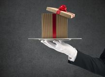 Waiter holds a Christmas present in a tray stock photo