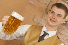 Waiter holds glass of beer Stock Image