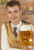 Waiter holds glass of beer Stock Photography