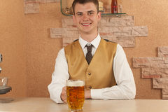 Waiter holds glass of beer Royalty Free Stock Photo