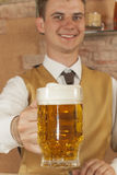 Waiter holds glass of beer Stock Photo