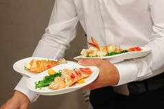 Waiter holds plates with lobsters Stock Photos
