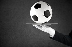 Waiter that holds a tray with soccer ball. Concept of first class service on soccer royalty free stock photo