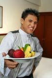 Waiter at hotel room. Waiter showing fruit at hotel room with smile, focus on fruit royalty free stock photo