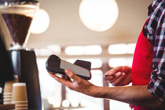 Waiter inserting customer's credit card into credit card machine Royalty Free Stock Images