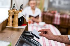 Waiter inserts the card into a computer terminal Royalty Free Stock Photo