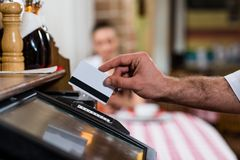 Waiter inserts the card into a computer terminal Stock Images
