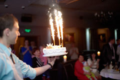 Waiter introducing a birthday cake with the firework in the ball Royalty Free Stock Photo