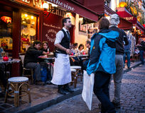 Waiter invites couple into his restaurant on Montmartre in Paris Stock Photos