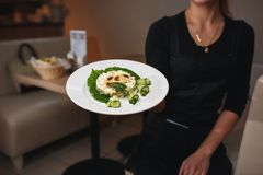 The waiter keeps the dish with Russian salad decorated with mushrooms and fresh cucumbers. Chef holding plate with tasty and royalty free stock images