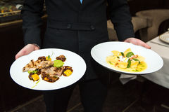 Waiter keeps meals with food. Waiter keeps plates with food Stock Photography