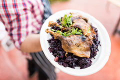 Waiter with large platter- duck confit and wine braised cabbage Stock Photography