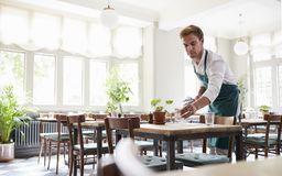 Waiter Laying Tables In Empty Restaurant royalty free stock images