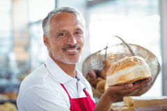 Waiter looking at camera and holding freshly baked bread Stock Photos