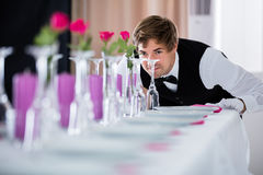 Waiter Looking At Table Arrangement. Handsome Waiter Looking At Wedding Table Arrangement At Restaurant royalty free stock image