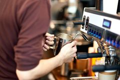 Waiter is making coffee on a modern coffee machine royalty free stock photography