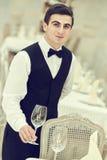 Waiter man serving banquet table at restaurant Royalty Free Stock Photos