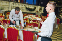 Waiter man serving in restaurant Stock Image