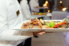 Waiter with Meat on Tray Stock Image