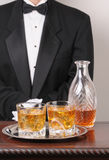Waiter with mixed drinks on tray. Waiter in tuxedo with Cocktails and Decanter on tray and wood table vertical format torso only royalty free stock photography