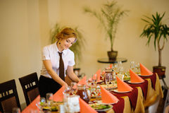 Waiter near the table with food Royalty Free Stock Photos