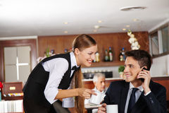 Waiter offering coffee to business man Royalty Free Stock Image