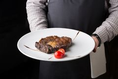 Waiter offering delicious restaurant dish. Rib eye steak decorated with tomato in unrecognizable male hands. Copy space on dark background stock images