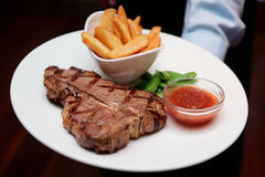 Waiter offering T-bone steak with french fries. And hot sauce Royalty Free Stock Photos