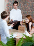 The waiter offers the menu to the visitors Royalty Free Stock Photos