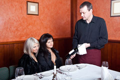 The waiter offers wine visitors Royalty Free Stock Photos