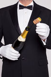 Waiter opening a bottle of champagne Royalty Free Stock Photography
