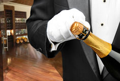 Waiter opening bottle of champagne. Closeup of a waiter opening a bottle of champagne with a wine cellar in the background stock images