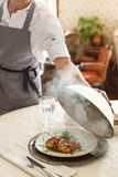 Waiter opens the lid of the dish. In restaurant royalty free stock images