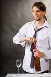 Waiter opens wine bottle. Winery serving tasting alcohol liquor concept. Waiter opens wine bottle. Young male sommelier pulls out cork royalty free stock photography