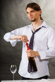 Waiter opens wine bottle. Winery serving tasting alcohol liquor concept. Waiter opens wine bottle. Young male sommelier pulls out cork stock photo