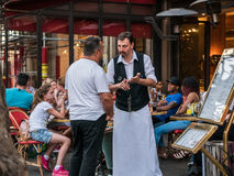 Waiter and patron in intense conversation at sidewalk cafe, Paris Royalty Free Stock Photography