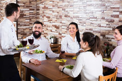 Waiter placing order in restaurant. Young waiter placing order in front of guests in rustic restaurant Stock Photography