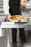 Waiter Placing Pasta Dishes On Tray. Midsection of waiter placing pasta dishes on tray in commercial kitchen Stock Images