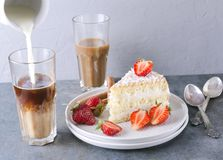 Pouring milk into the glass of coffee, tasty slice of sponge cake with strawberries on the plate. Coffee time with delicious sweet. Waiter pourig hot water onto stock images