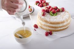 Waiter pourig hot water onto the tea bag. Tea time, delicious sponge cake with cream and fruits. Setting the table during tea time.Fresh baked sponge cake with stock photo
