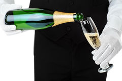 Waiter pouring champagne into glass. Isolated on white background Royalty Free Stock Photos