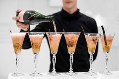 Waiter pouring champagne in glasses. Crop view of faceless waiter in black shirt making alcoholic cocktails and adding champagne in glasses Royalty Free Stock Photos