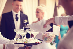 Waiter pouring champagne in the glasses. With groom and bride in background Stock Image