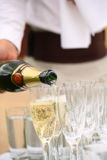 Waiter pouring champagne in glasses on the table. Waiter holding a napkin in one hand pouring champagne in glasses on the table Stock Image