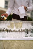 Waiter pouring champagne in glasses on the table Royalty Free Stock Images