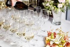 Waiter pouring champagne in the party event. Reception at the wedding party or Banquet for the anniversary. Waiter pouring champagne in the party event stock image