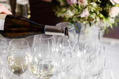 Waiter pouring champagne in the party event. Reception at the wedding party or Banquet for the anniversary. Waiter pouring champagne in the party event royalty free stock photo
