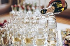 Waiter pouring champagne in stylish glasses at luxury wedding re Royalty Free Stock Images