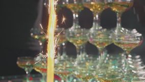 Waiter pouring champagne in glasses at pyramid with confetti and fountains stock video footage
