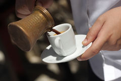 Waiter is pouring coffee Royalty Free Stock Photography
